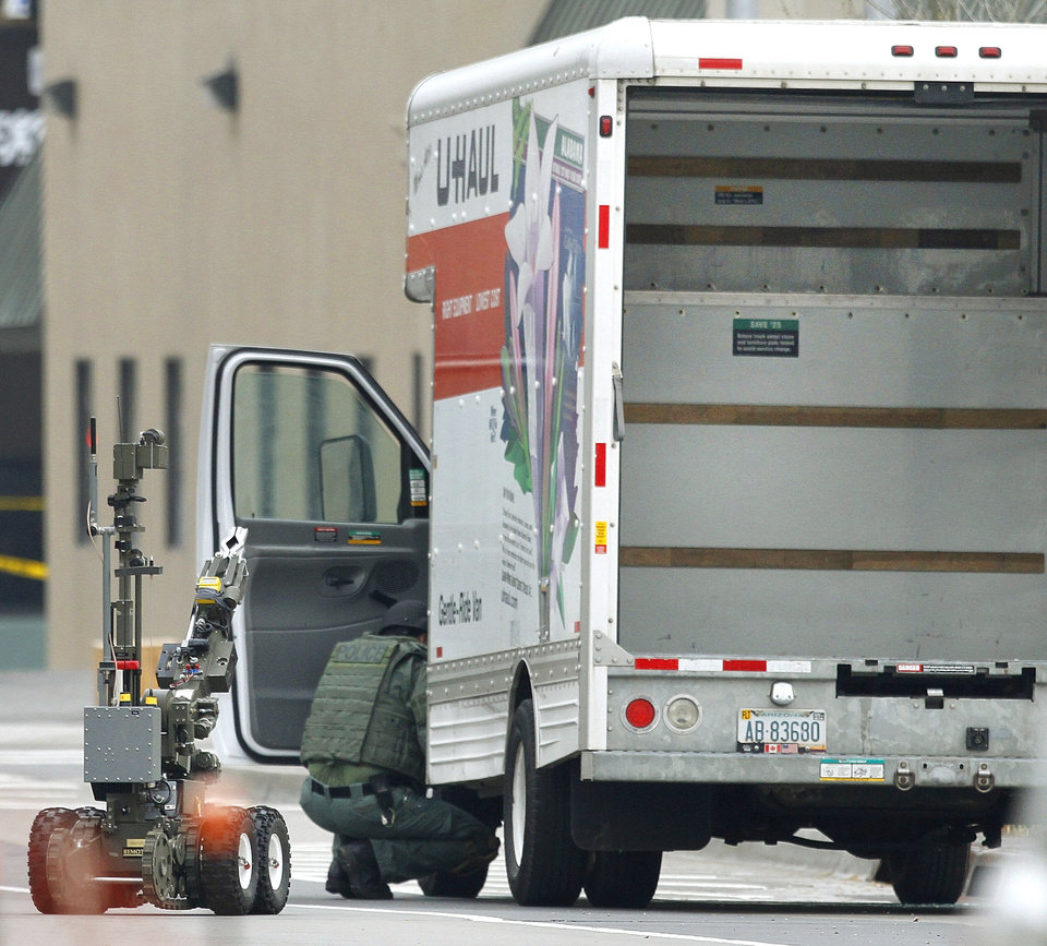 BOMB SCARE: A member of the Oklahoma City Police Bomb Squad searchs a U-Haul truck parked on Walker Avenue in downtown Oklahoma City , Wednesday April 17, 2013. Photo By Steve Gooch, The Oklahoman ORG XMIT: OKC1303121532440650