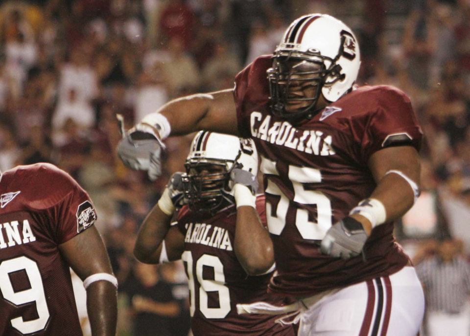 Photo - FILE - In this Sept. 1, 2005 file photo, South Carolina's Stanley Doughty (55) celebrates with his teammates after stopping Central Florida from scoring during an NCAA college football game in Columbia, S.C. Doughty is one of the plaintiffs in a class-action head injury lawsuit working its way through federal court in Chicago. The NCAA and the plaintiffs announced a settlement on Tuesday, July 29, 2014.  (AP Photo/Perry Baker, File)
