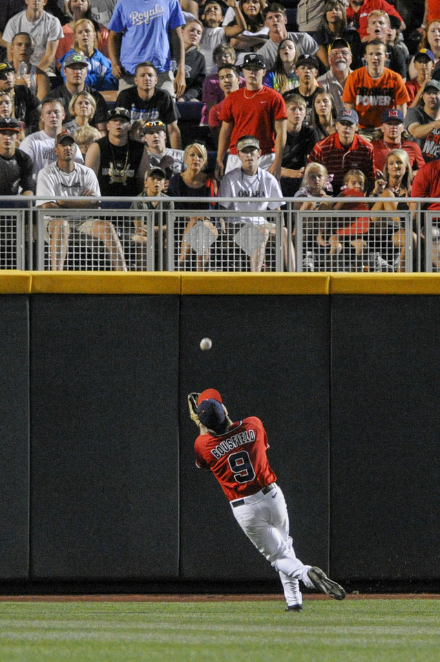 Photo - Mississippi center fielder Auston Bousfield (9) catches a fly ball hit by Virginia's Derek Fisher in the seventh inning of an NCAA baseball College World Series game in Omaha, Neb., Sunday, June 15, 2014. (AP Photo/Eric Francis)