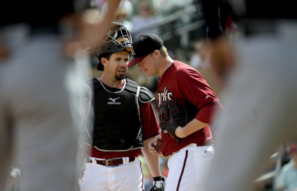 Photo - Arizona Diamondbacks catcher Tuffy Gosewisch, left, talks with starting pitcher Archie Bradley after Seattle Mariners' Endy Chavez stole third during the first inning of a spring exhibition baseball game in Scottsdale, Ariz., Thursday, March 13, 2014. (AP Photo/Chris Carlson)