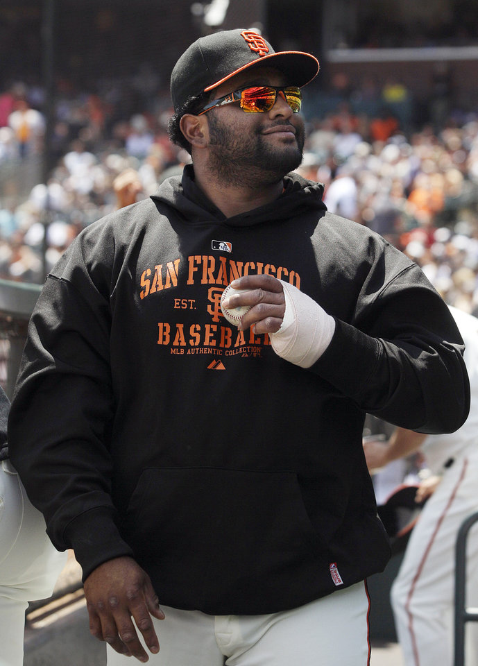 Photo -   San Francisco Giants third baseman Pablo Sandoval smiles from the dugout during a baseball game against the Milwaukee Brewers in San Francisco, Sunday, May 6, 2012. (AP Photo/Jeff Chiu)