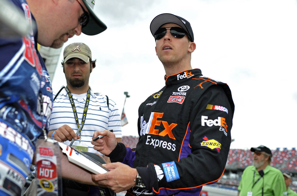 Photo - NASCAR Sprint Cup series driver Denny Hamlin signs autographs for fans during practice at the Talladega Superspeedway in Talladega, Ala., Friday, May 3, 2013. (AP Photo/Rainier Ehrhardt)