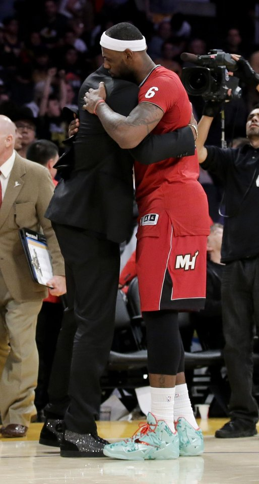Photo - Miami Heat forward LeBron James, right, hugs Los Angeles Lakers guard Kobe Bryant after the Heat's 101-95 win in an NBA basketball game in Los Angeles, Wednesday, Dec. 25, 2013. (AP Photo/Chris Carlson)