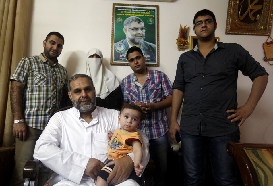 Photo - In this Tuesday, June 25, 2013, members of Rantisi family pose for a photo at their house in Gaza City. From right, counter-clockwise, are Anaz, 22, Malik, 18, Kifah, Baraa's mother, 47, Baraa, 23, Mohammed his father, 55, and Baraa's 10-month-old son Mohammed. On the day of his induction, Baraa Rantisi was told to wait near a mosque. A white car drove up. Secret passwords were exchanged. And then he was sworn into the Muslim Brotherhood, an exclusive movement that sees itself on a divine mission to establish Islamic rule. AP reporters got rare access to the Rantisi family, the closest thing to a royal clan in the Brotherhood in Gaza, at a time when the movement is under siege throughout the region. (AP Photo/Hatem Moussa)
