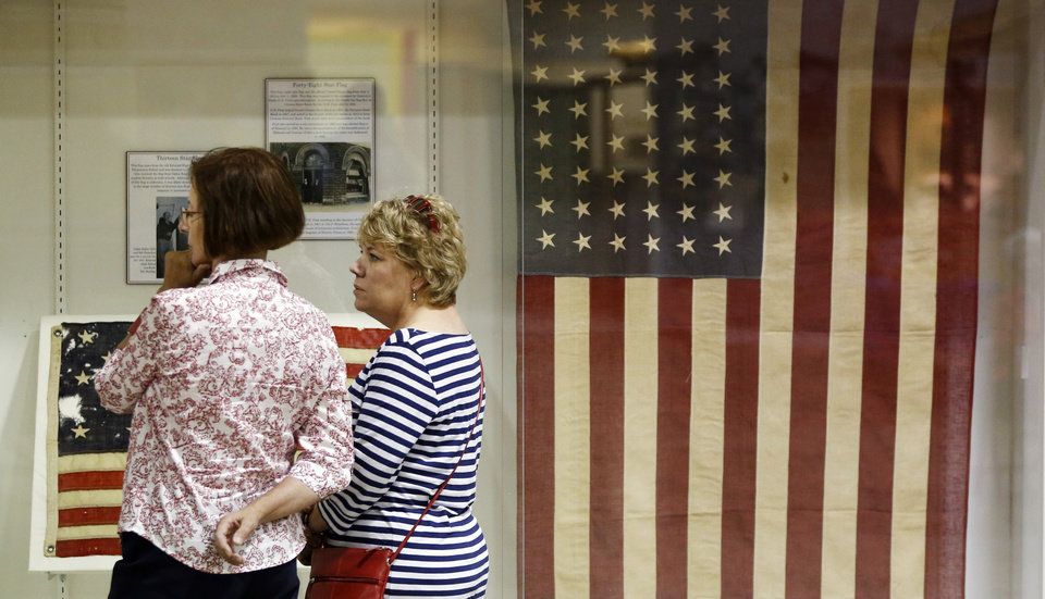 """Photo -  Edmond City Ccouncilwoman Elizabeth Waner, left, and Beth Kerr read information about the history of the American flag during """"Raise It Up!"""" at the Edmond Historical Society and Museum. Groups around the country gathered Saturday, in recognition of Flag Day, to sing the national anthem. PHOTO BY NATE BILLINGS, THE OKLAHOMAN   NATE BILLINGS - NATE BILLINGS"""