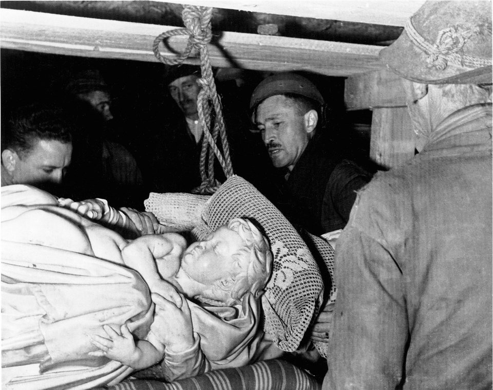 Photo - This photo provided by The Monuments Men Foundation for the Preservation of Art of Dallas, shows Monuments Man George Stout, second from right, with others as they remove Michelangelo's Bruges Madonna from the salt mine in Altaussee, Austria, July 10, 1945. Priceless works of art from the salt mine posed problems for Stout unlike any ever contemplated. Stout constructed a pulley to lift Bruges Madonna onto the salt cart to begin its long trip home to Belgium. From a fairy tale-inspiring castle in the Bavarian Alps to a serene sculpture of Mary and Jesus by Michelangelo tucked away in a church in Belgium, sites and works of art across Europe can give travelers a glimpse at the heroic work done by those who worked to save cultural treasures during World War II.  (AP Photo/National Archives and Records Administration)