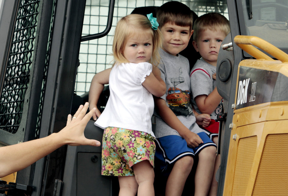"Grace, 7, Knox, 5, and Owen Westmoreland, 3, get to sit in the cab of a bulldozer at the annual ""Touch a Truck"" event on Saturday, April 28, 2012, in Norman, Okla.  Photo by Steve Sisney, The Oklahoman"