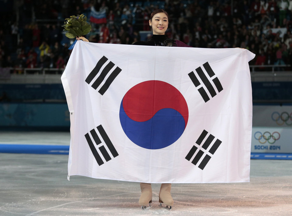 Photo - Yuna Kim of South Korea poses with the national flag as she celebrates her second place for the women's free skate figure skating final at the Iceberg Skating Palace during the 2014 Winter Olympics, Thursday, Feb. 20, 2014, in Sochi, Russia. Sotnikova placed first, followed by Kim and Kostner. (AP Photo/Ivan Sekretarev)
