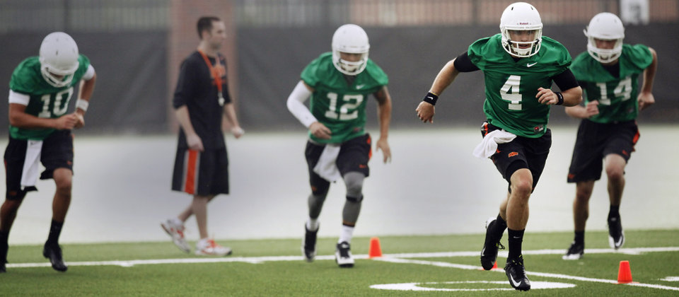 Photo - Oklahoma State quarterback J.W. Walsh (4) runs ahead of fellow quarterbacks Mason Rudolph (10), Daxx Garman (12), and Taylor Cornelius (14) during the first team practice of the fall at the Sherman E. Smith Training Facility on the campus of Oklahoma State University in Stillwater on August 1, 2014. Photo by KT King, The Oklahoman