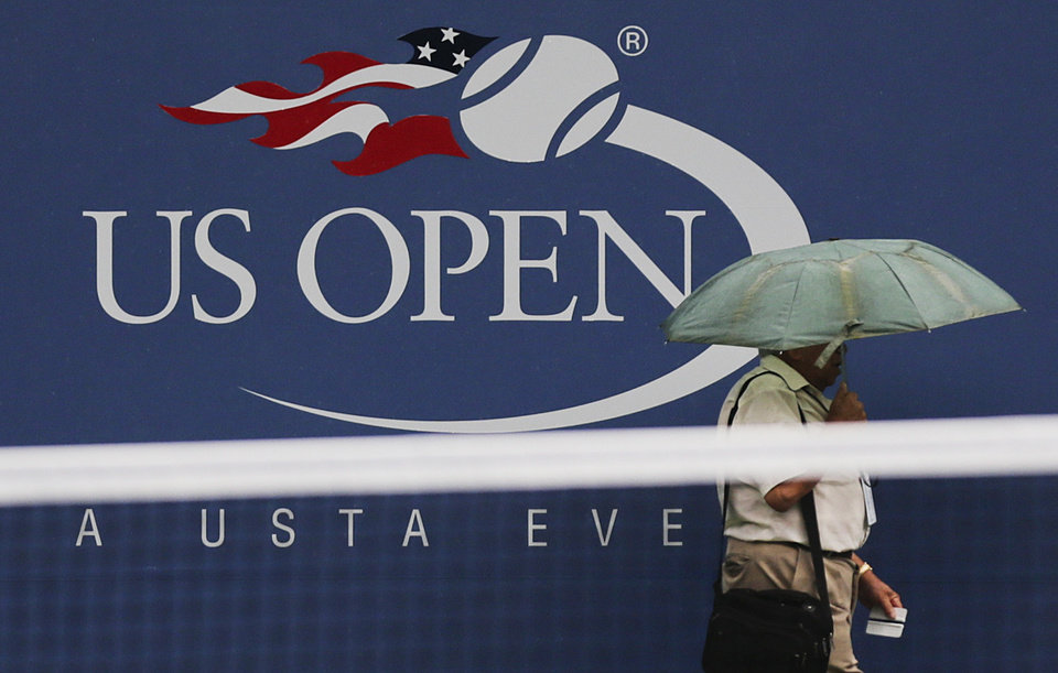 Photo -   A person passes a logo for the US Open before play is to resume at the 2012 US Open tennis tournament, Saturday, Sept. 8, 2012, in New York. (AP Photo/Charles Krupa)