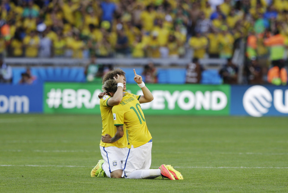 Photo - Brazil's Neymar hugs teammate David Luiz after a penalty shootout following regulation time during the World Cup round of 16 soccer match between Brazil and Chile at the Mineirao Stadium in Belo Horizonte, Brazil, Saturday, June 28, 2014. Brazil won 3-2 on penalties after a 1-1 tie. (AP Photo/Ricardo Mazalan)