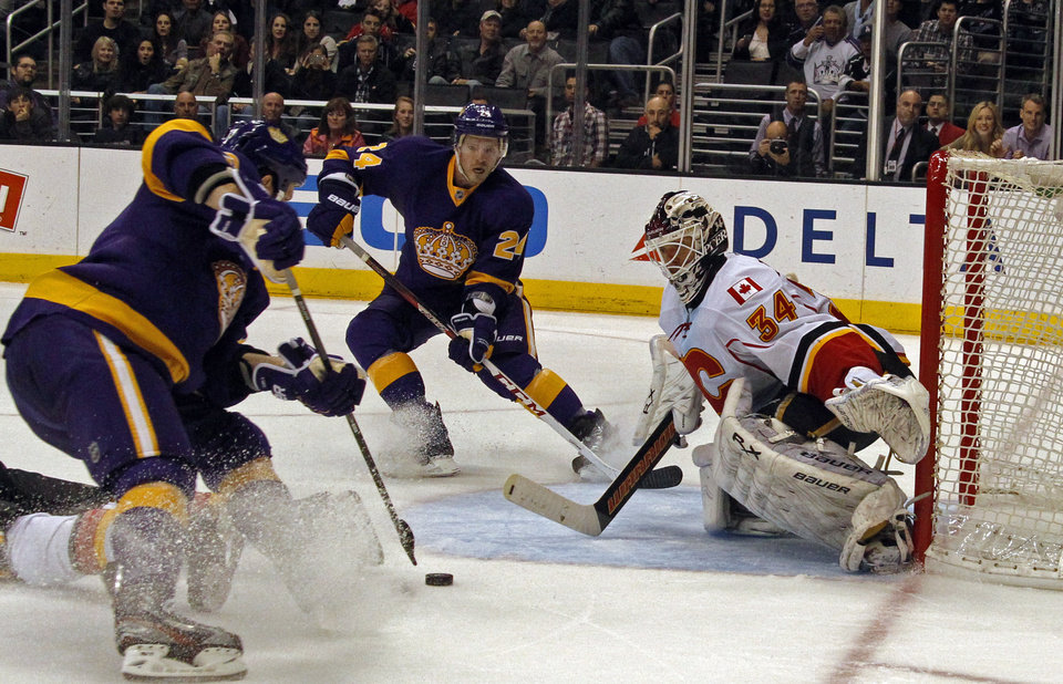 Los Angeles Kings left winger Kyle Clifford, left, maneuvers for a shot on Calgary Flames goalie Mikka Kiprusoff (34), of Finland, in the second period of an NHL hockey game in Los Angeles on Saturday, March 9, 2013. (AP Photo/Reed Saxon)
