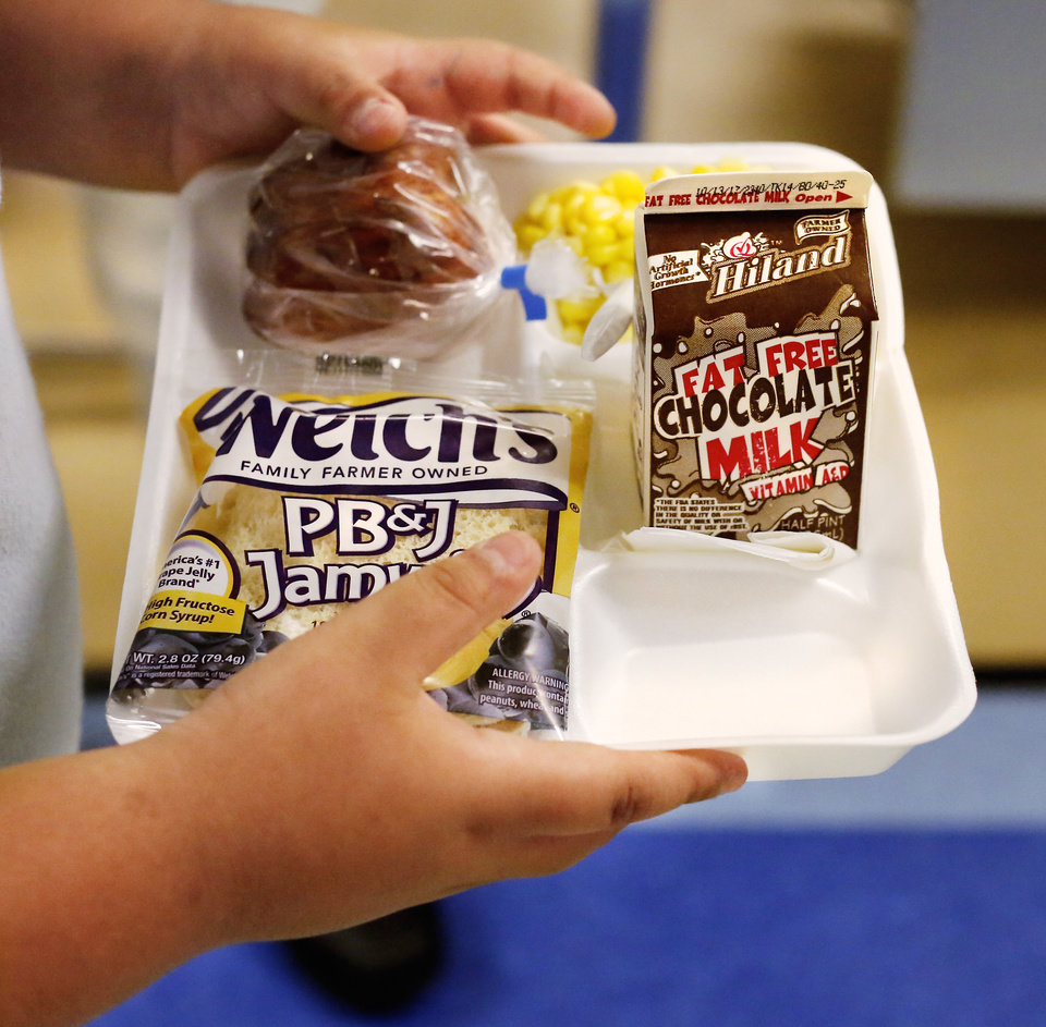 Photo -  A Eugene Field Elementary School student carries a lunch tray. [Photo by Jim Beckel, The Oklahoman]