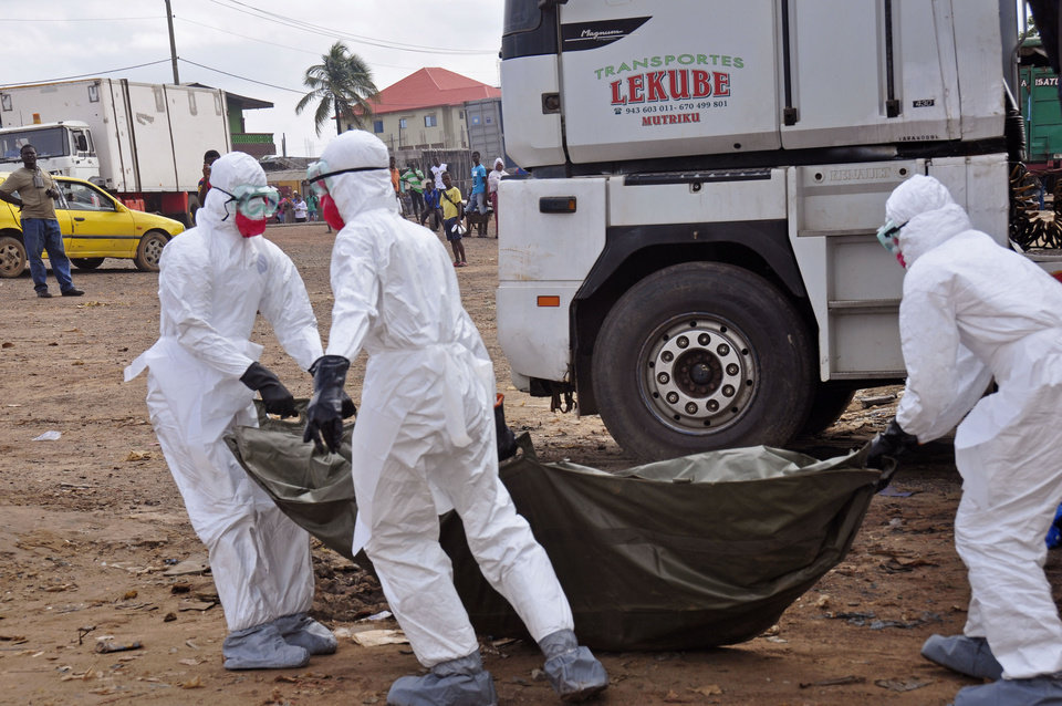 Photo - Health workers carry the body of a man suspected of dying from the Ebola virus and left in the street, as people watch in the background, in the capital city of Monrovia, Liberia, Tuesday, Aug. 12, 2014. The World Health Organization declared it's ethical to use untested drugs and vaccines in the ongoing Ebola outbreak in West Africa although the tiny supply of one experimental drug handed out to three people has been depleted and it could be many months until more is available. (AP Photo/Abbas Dulleh)