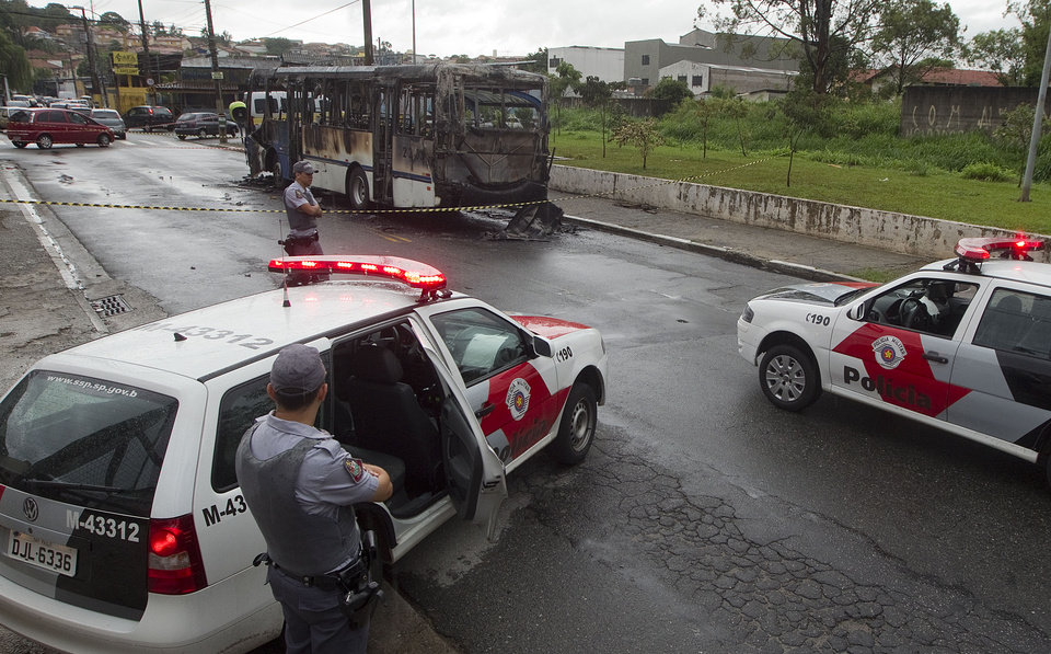 Police stand guard near a torched commuter bus in a suburb of Sao Paulo, Brazil, Monday, Nov. 12, 2012. Bus burnings were part of a wave of violence that left 31 dead over the weekend in Sao Paulo, according to police. (AP Photo/Andre Penner)