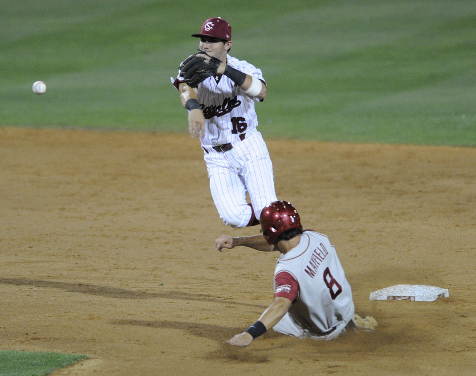 Photo - South Carolina's Chase Vergason (16) just misses a double play as Oklahoma's Jack Mayfield (8) slides underneath in the seventh inning of an NCAA college super regional baseball tournament game in Columbia, S.C., Saturday, June 9, 2012. (AP Photo/Mary Ann Chastain) ORG XMIT: SCMC116