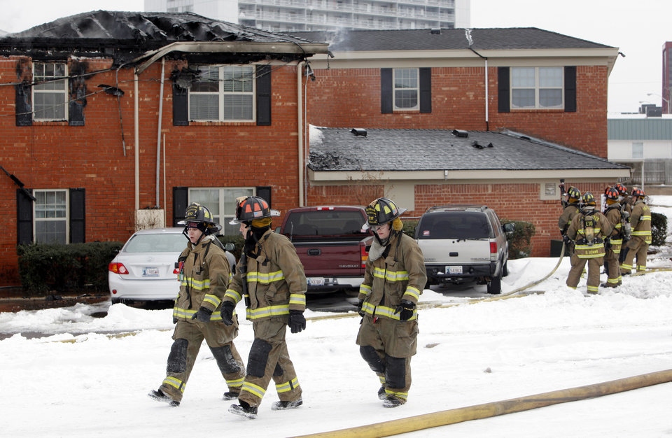 Oklahoma City firefighters walk through snow after fighting a fire at the Tara Condominiums at NW 62 and Brookline Ave. in Oklahoma City, Thursday, Feb. 3, 2011. Photo by Nate Billings, The Oklahoman