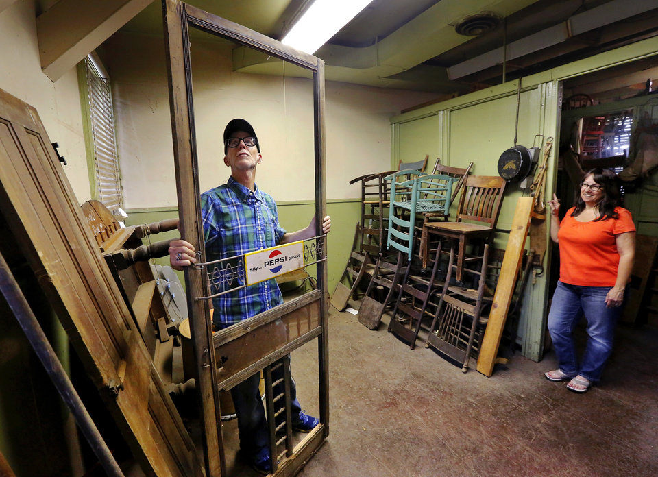 Photo -  Max Hester looks at an old screen door that once was the front door to a drug store in Choctaw. At right is his sister-in-law, Liz Hester. Photo was taken May 28 inside his deceased parents' antique shop in Choctaw. Photo by Jim Beckel, The Oklahoman   Jim Beckel -