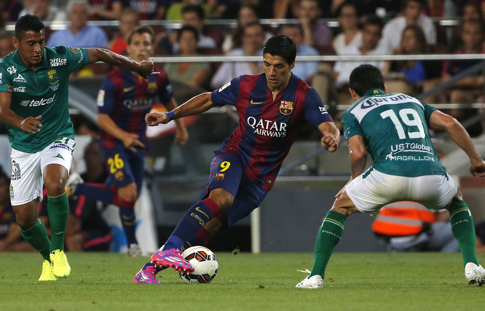 Photo - Barcelona's Luis Suarez from Uruguay fights for the ball against Leon's Luis Antonio Delgado, left, and Jonny Magallon, during the Joan Gamper trophy friendly soccer match between Barcelona and Leon at the Camp Nou stadium in Barcelona, Spain, Monday, Aug. 18, 2014. (AP Photo/Emilio Morenatti)