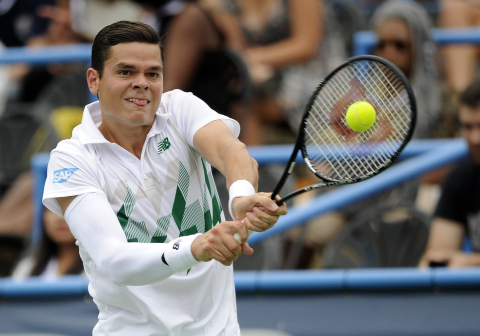 Photo - Milos Raonic, of Canada, returns the ball against Steve Johnson during a match at the Citi Open tennis tournament, Friday, Aug. 1, 2014, in Washington. (AP Photo/Nick Wass)