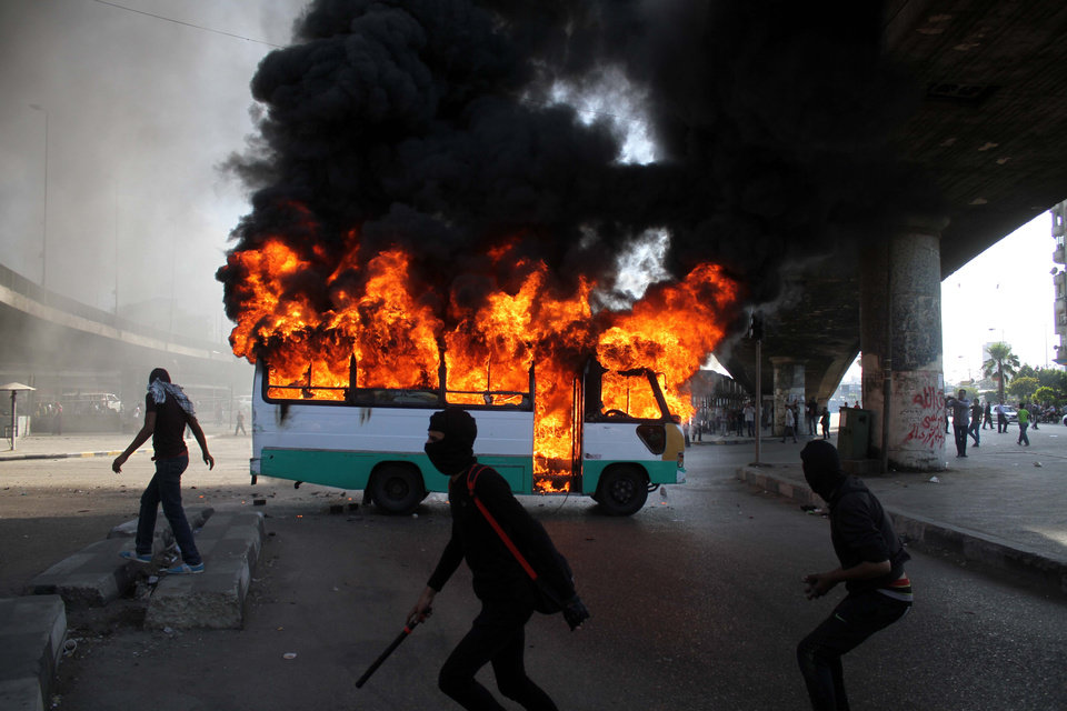 "Egyptian protesters clash near a bus belonging to Muslim Brotherhood supporters burns after it was reportedly set alight by anti- government protesters in Cairo, Egypt, Friday, April 19, 2013. Clashes erupted Friday between several hundred opponents and supporters of Egypt's Islamist president during a rally by his allies calling on him to ""cleanse the judiciary"" of alleged supporters of the old regime. (AP Photo/Mostafa Elshemy)"