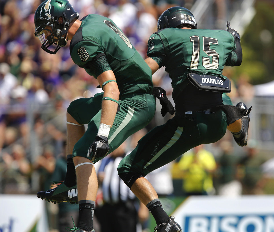 Photo - Wide receivers Eric DeLay, left, and Derek Serowski jump into the air, celebrating the Bison second touchdown in the first quarter when Serowski scored on a pass reception. The Oklahoma Baptist University football team  took to the field on the school's Shawnee campus for the first time in more than seven decades when they hosted the Southwestern College(Kansas) Moundbuilders  at Bison Field in the Eddie Hurt Athletic Center on Saturday, Aug. 31, 2013. The Bison team was defeated today, 26-22. Prior to the 2013 season opener, the Bison football team played their last game in 1940. Photo  by Jim Beckel, The Oklahoman.         The Oklahoma Baptist University football team  took to the field on the school's Shawnee campus for the first time in more than seven decades when they hosted the Southwestern College(Kansas) Moundbuilders  at Bison Field in the Eddie Hurt Athletyic Center on Saturday, Aug. 31, 2013. The Bison team was defeated today, 26-22. Prior to the 2013 season opener, the Bison football team played their last game in 1940. Photo  by Jim Beckel, The Oklahoman.
