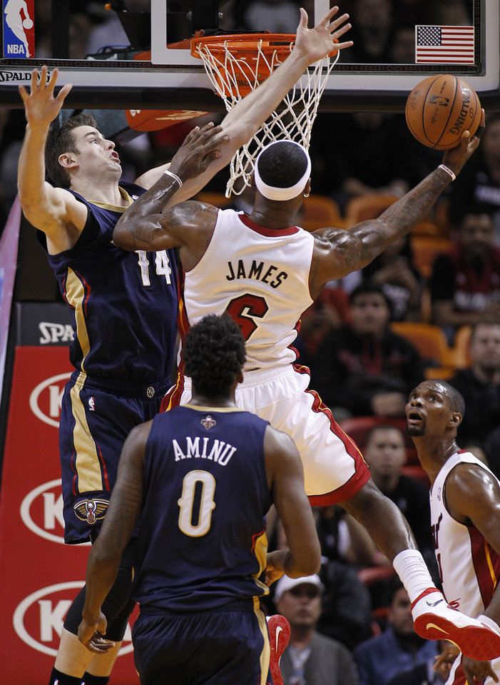 Photo - Miami Heat's LeBron James (6) goes to the basket against New Orleans Pelicans' Jason Smith (14) during the first half of an NBA basketball game in Miami, Tuesday, Jan 7, 2014. (AP Photo/Joel Auerbach)