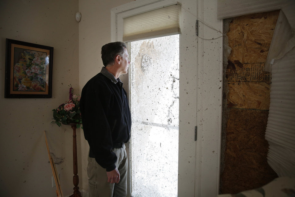 Photo - Emmett Wingfield stares out of his damaged home window on Wednesday, March 2, 2016, after storms struck Tuesday in Bessemer, Ala. Wingfield says he can't believe all of the damage done to his home and is glad he and his wife were not home during the storms.  Forecasters say a tornado that severely damaged homes and trees in the Birmingham suburb has been determined as an EF2, with winds of between 120 and 125 mph.  (AP Photo/Brynn Anderson)