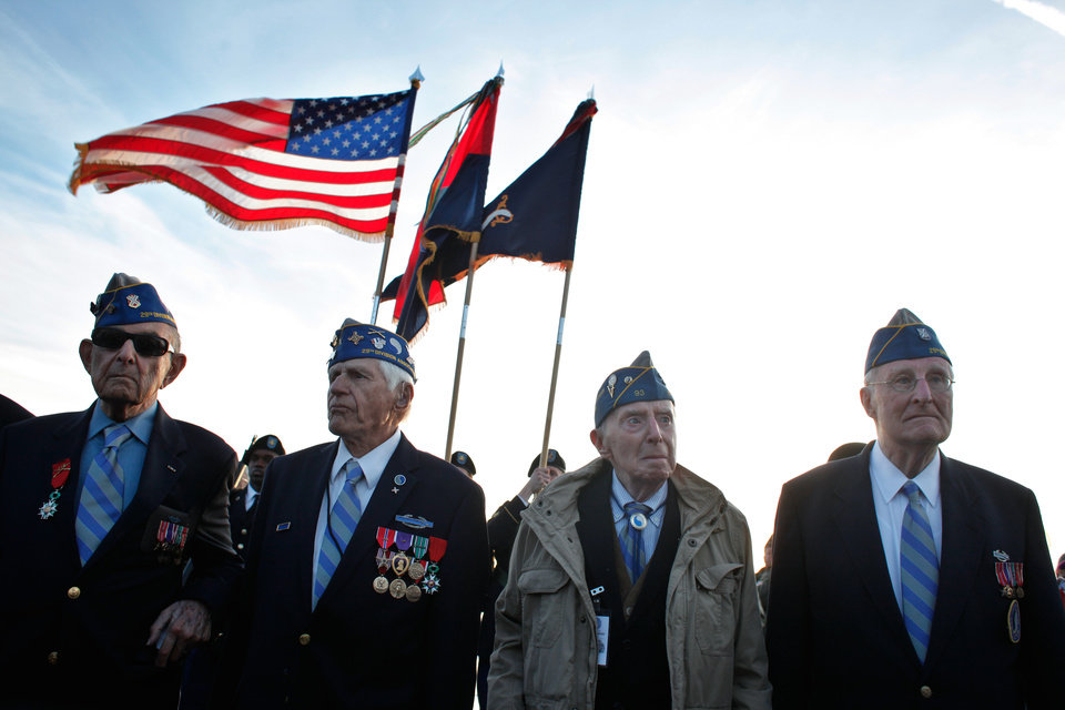 Photo - CORRECTS SPELLING FROM BAUMGARTER TO BAUMGARTEN, AND CORRECTS STATES OF RESIDENCE FOR MELINKOFT FROM RHODE ISLAND TO MARYLAND AND FOR McCARTHY FROM MARYLAND TO RHODE ISLAND - From left, World War II veterans of the U.S. 29th Infantry Division, Hal Baumgarten, 90 from Pennsylvania, Steve Melnikoff, 94, from Maryland, Don McCarthy, 90 from Rhode Island, and Morley Piper, 90, from Massachusetts, attend a D-Day commemoration, on Omaha Beach, western France , Friday June 6, 2014. Veterans and Normandy residents are paying tribute to the thousands who gave their lives in the D-Day invasion of Nazi-occupied France 70 years ago. World leaders and dignitaries including President Barack Obama and Queen Elizabeth II will gather to honor the more than 150,000 American, British, Canadian and other Allied D-Day troops who risked and gave their lives to defeat Adolf Hitler's Third Reich. (AP Photo/Thibault Camus)