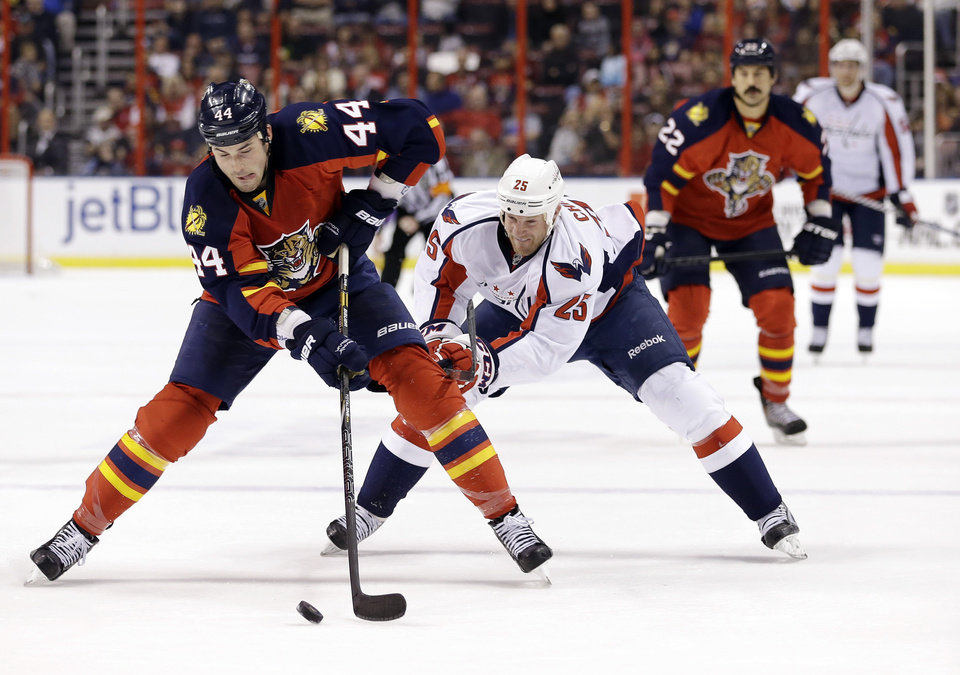 Photo - Florida Panthers defenseman Erik Gudbranson (44) and Washington Capitals left wing Jason Chimera (25)  battle for the puck during the first period of an NHL hockey game, Tuesday, Feb. 12, 2013 in Sunrise, Fla. (AP Photo/Wilfredo Lee)