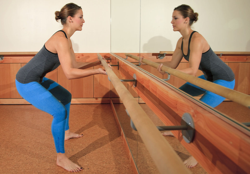 Model Emoly demonstrates Sumo, a Barre3 posture. Underhand grip the barre, bend your knees over your ankles and hinge forward at the waist. Spine is elongated reaching the behind you. Targets the hamstrings and inner thighs. Photo by Chris Landsberger, The Oklahoman. <strong>CHRIS LANDSBERGER</strong>