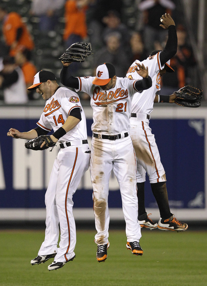 Photo -   From left, Baltimore Orioles' Nolan Reimold, Nick Markakis and Adam Jones leap after the Orioles' 5-2 win in a baseball game against the Toronto Blue Jays in Baltimore, Thursday, April 26, 2012. (AP Photo/Patrick Semansky)