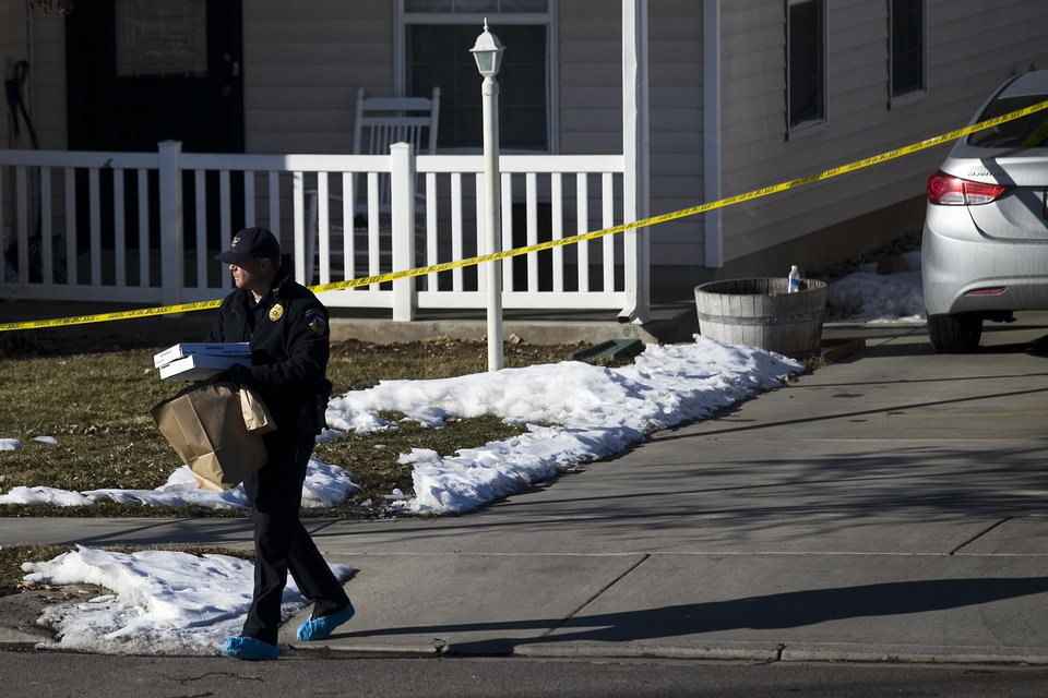 Photo - Investigators remove evidence from a home, Friday, Jan. 17, 2014, in Spanish Fork, Utah,  where five people were found dead on Thursday.  A 34-year-old officer shot and killed his wife, mother-in-law and two young children and turned the gun on himself, authorities said Friday.  Spanish Fork police said the five were found dead about 11 p.m. Thursday, when co-workers reported Joshua Boren didn't show up for his night shift as a patrol officer at the Lindon Police Department. (AP Photo/Daily Herald, Mark Johnston)
