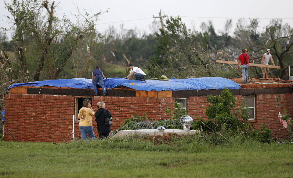 Photo - People work to cover a home that was damaged by a tornado in Carney Okla., on Sunday, May 19, 2013. Photo by Bryan Terry, The Oklahoman