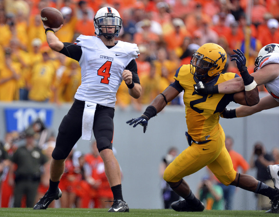Photo - Oklahoma State quarterback J.W. Walsh (4) attempts a pass as West Virginia's Brandon Golson rushes in during the second quarter of an NCAA college football game in Morgantown, W.Va., on Saturday, Sept. 28, 2013. (AP Photo/Tyler Evert) ORG XMIT: WVTE103