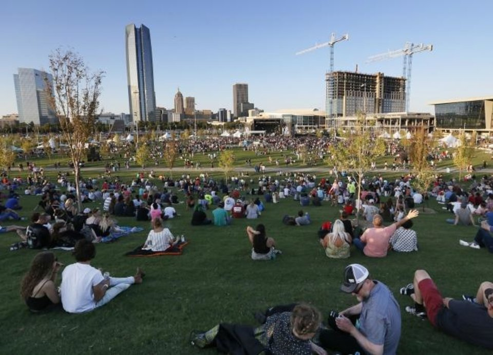 Photo -  Oklahoma City's skyline is visible from the hill as Republican Hair performs during Friday's  grand opening of Scissortail Park. [Nate Billings/The Oklahoman]