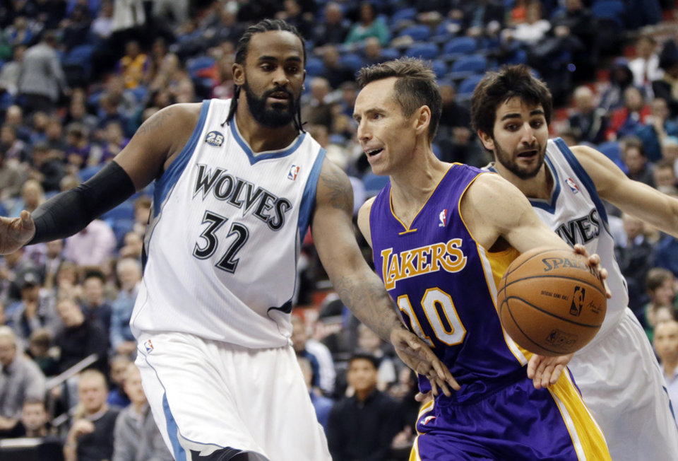Photo - Los Angeles Lakers' Steve Nash, center, drives as Minnesota Timberwolves' Ronny Turiaf, left, of France, and Ricky Rubio, of Spain, defend during the second half of an NBA basketball game, Tuesday, Feb. 4, 2014, in Minneapolis. The Timberwolves won 109-99. Nash had been sidelined since Nov. 10 because of nerve problems in his back. (AP Photo/Jim Mone)