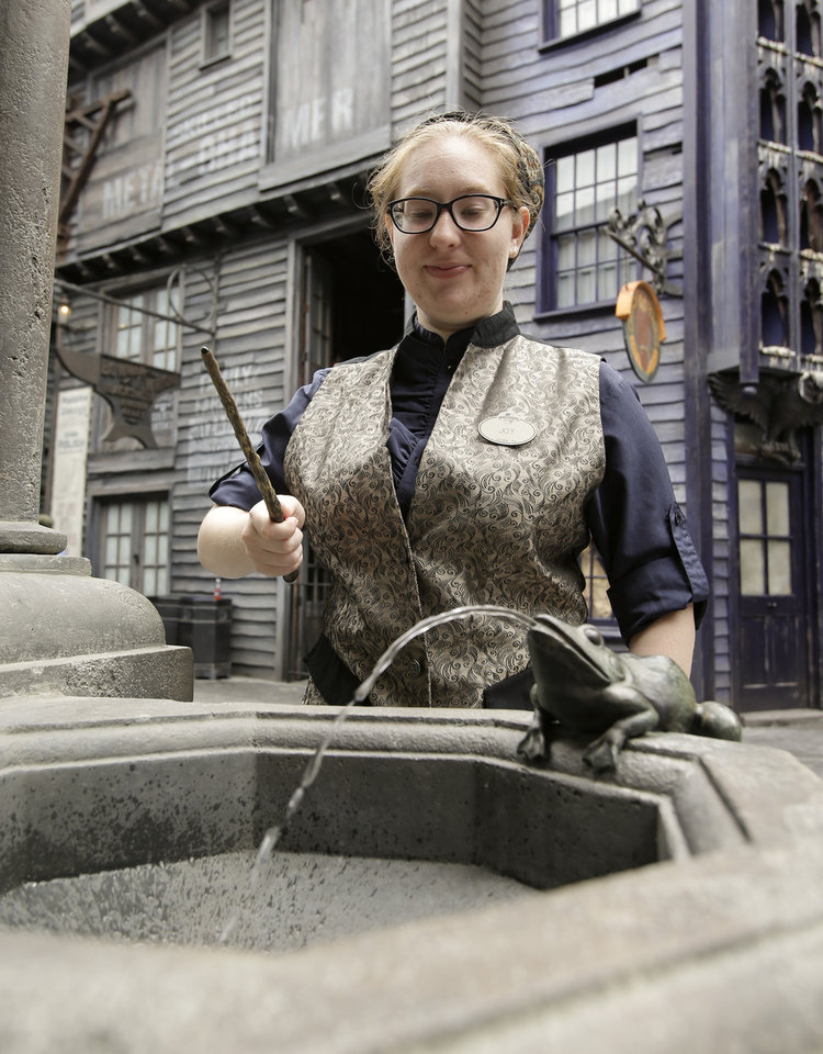 Photo - Joy Gorrell waves an interactive wand that guests can purchase to create magic by waving at various locations such as this frog fountain in the park during a preview of Diagon Alley at the Wizarding World of Harry Potter at Universal Orlando, Thursday, June 19, 2014, in Orlando, Fla. (AP Photo/John Raoux)