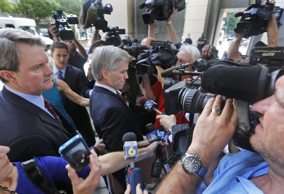 Photo - Former Virginia Gov. Bob McDonnell, center, tries to move through the throng of media as he and his attorney, John Brownlee,  left, arrive at federal court in Richmond, Va., Tuesday, Aug. 19, 2014. McDonnell is presenting the second day of his defense on corruption charges. (AP Photo/Steve Helber)