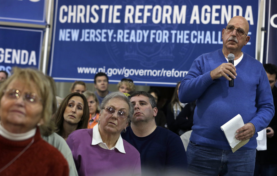 Photo - People look on as Mike Grasso, right, asks New Jersey Gov. Chris Christie a question during a town hall meeting at Saint Mary's of The Pines Church Parish Wednesday, Jan.16, 2013, in Manahawkin, N.J., Grasso wanted to know when the dredging and removal of debris will begin in the bay area of Manahawkin. Christie said there are possibly cars, boats and houses submerged in waters around the Jersey shore because of Superstorm Sandy. (AP Photo/Mel Evans)