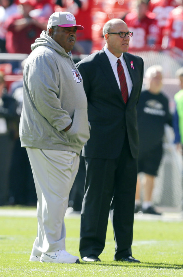 FILE - In this Oct. 7, 2012, file photo, Kansas City Chiefs head coach Romeo Crennel, left, and general manager Scott Pioli watch the team warm up prior to an NFL football game against the Baltimore Ravens in Kansas City, Mo.  Police say Chiefs player Javon Belcher fatally shot his girlfriend early Saturday, Dec. 1, 2012, in Kansas City, Mo., then drove to Arrowhead Stadium and committed suicide in front of his coach and general manager. (AP Photo/Ed Zurga, File)