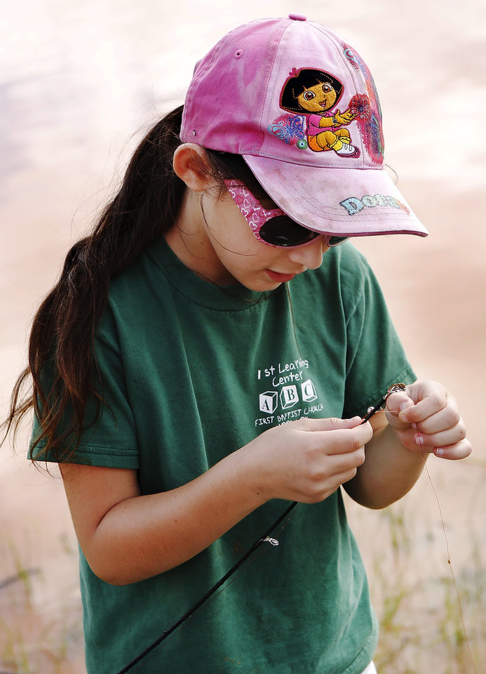Photo - Abigail Suttle, 8, removes weeds from her hook before she changes her bait, switching to live worms. Moore hosted its annual kids fishing derby Saturday morning, July 27, 2013,  at Buck Thomas Park.  As part of the event this year, a charity called the Tackle the Storm Foundation handed out rods and reels to tornado victims. Several bass fishing pros from Oklahoma attended the event to help distribute the fishing equipment and share fishing tips with the young anglers. An event official  said about 250 children participated in the fishing derby. Photo  by Jim Beckel, The Oklahoman.