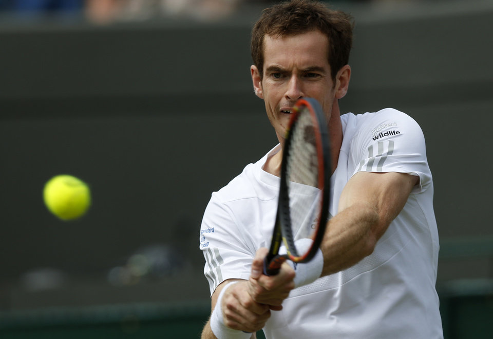 Photo - Andy Murray of Britain returns to Biaz Rola of Slovenia during their men's singles match at the All England Lawn Tennis Championships in Wimbledon, London, Wednesday, June 25, 2014. (AP Photo/Sang Tan)