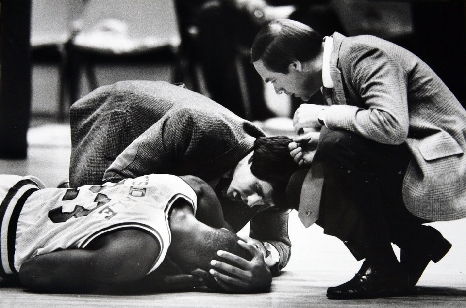 Former OU basketball player Wayman Tisdale. Wayman Tisdale is tended to after suffering a gash across his tongue early in Saturday's game as coach Billy Tubbs looks on. Photo taken , published 2-5-83 in The Daily Oklahoman        Staff Photo by Doug Hoke    ORG XMIT: KOD
