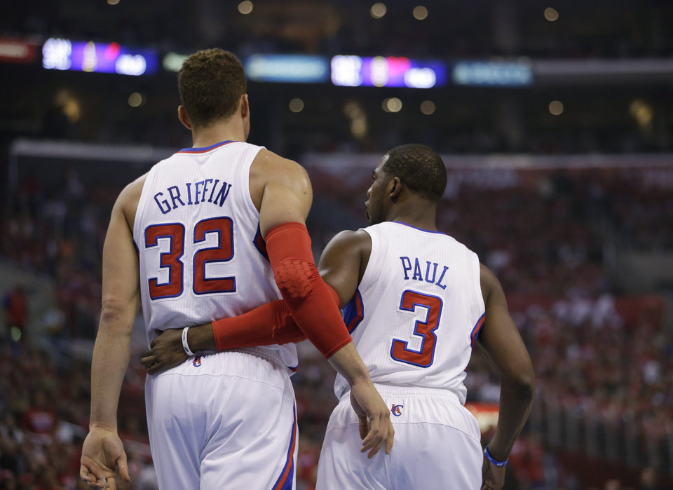 Photo - Los Angeles Clippers' Blake Griffin, left, chats with Chris Paul during the first half in Game 5 of a first-round NBA basketball playoff series against the Memphis Grizzlies in Los Angeles, Tuesday, April 30, 2013. (AP Photo/Jae C. Hong)