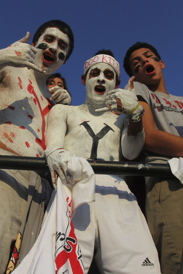 Photo - Yukon High School seniors Alex Serrano, Anthony McCollum and Xavier Hill, left to right, cheer on the Millers during the Mustang - Yukon High School football  season opener Friday night at Bronco Stadium in Mustang. Photo by Hugh Scott, for the Oklahoman