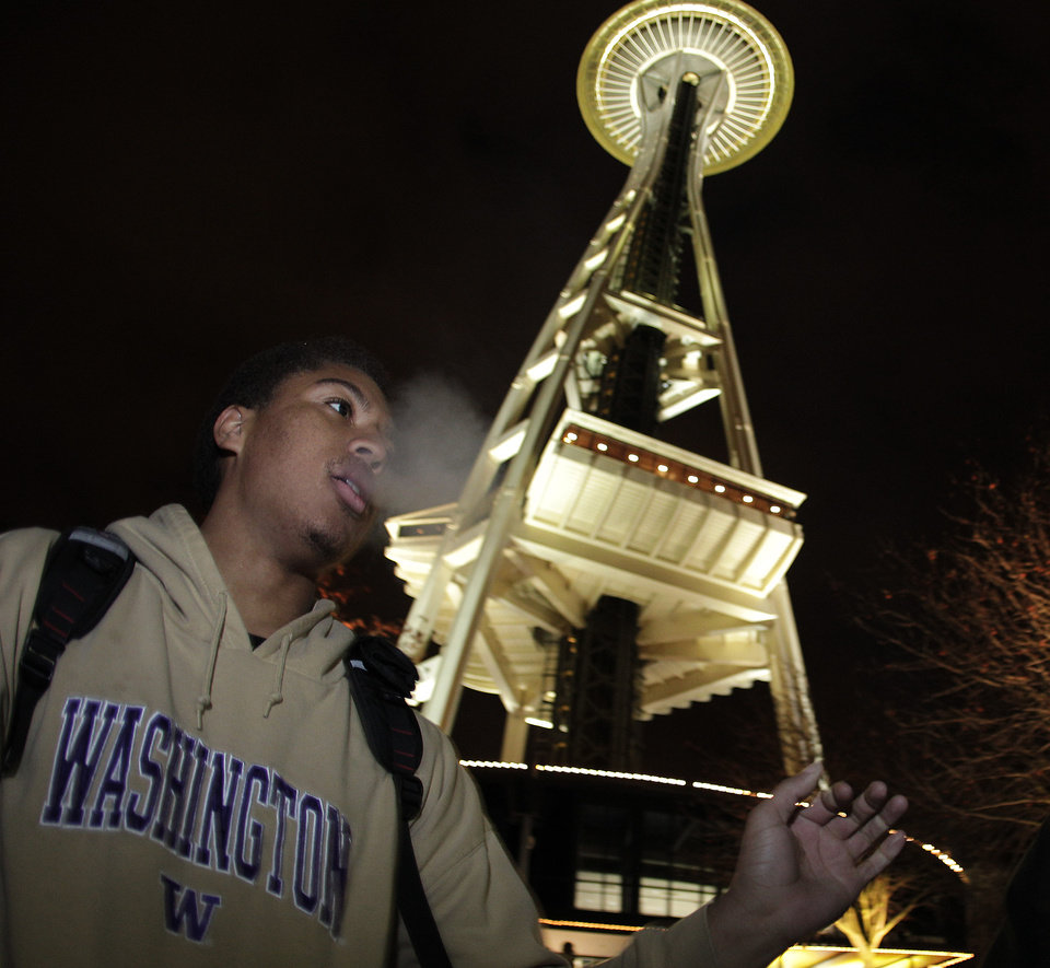 Photo - Andre Edwards smokes marijuana, Thursday, Dec. 6, 2012, just after midnight at the Space Needle in Seattle. Possession of marijuana became legal in Washington state at midnight, and several hundred people gathered at the Space Needle to smoke and celebrate the occasion, even though the new law does prohibit public use of marijuana. (AP Photo/Ted S. Warren)