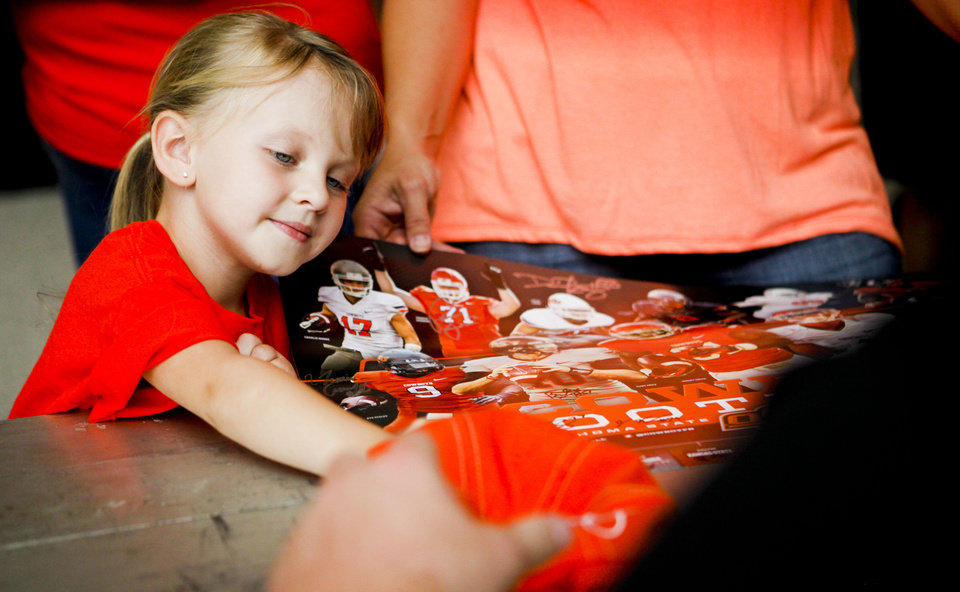 Tassi Day, 4, of Yale, Okla., has a hat signed by football players at fan appreciation day at Gallagher Iba Arena in Stillwater on August 3, 2013. KT King, For The Oklahoman