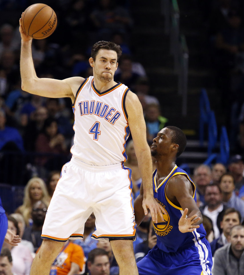 Photo - Oklahoma City's Nick Collison (4) looks to get by Golden State's Harrison Barnes (40) during the NBA game between the Oklahoma City Thunder and the Golden State Warriors at the Chesapeake Energy Arena, Sunday, Nov. 23, 2014.  Photo by Sarah Phipps, The Oklahoman