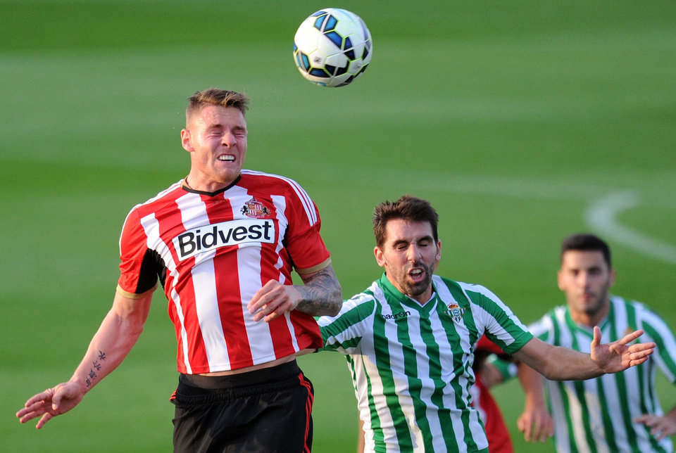 Photo - Sunderland's Connor Wickham, left, and Real Betis' Figueras Jordi in action during their pre-season friendly at Heritage Park, Sunderland, Thursday Aug. 7, 2014.  (AP Photo / Owen Humphreys, PA) UNITED KINGDOM OUT - NO SALES - NO ARCHIVES